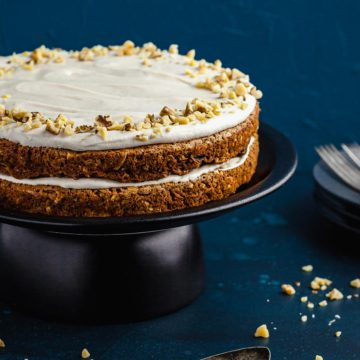 Two layer carrot cake on cake stand.
