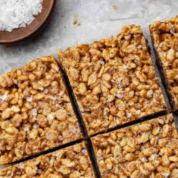 Close up view of cut salted caramel vegan rice crispy treats with a small bowl of sea salt in the corner.