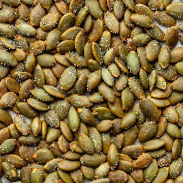 Close up of roasted pepitas on a baking sheet.
