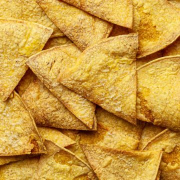 Close up of a pile of baked oil-free vegan tortilla chips.