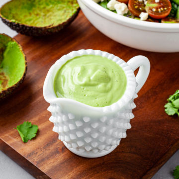Container of avocado ranch dressing sitting on a cutting board.