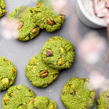 Overhead view of vegan matcha cookies with pistachios on a concrete background with out-of-focus cherry blossoms framing them.